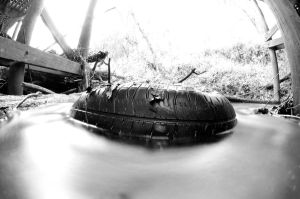 Tire in creek by lamorth-the-seeker