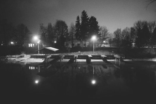one with night view of small marina from across by Maclunar