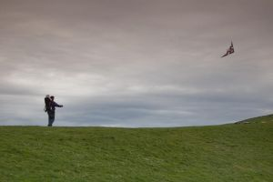 Man and Son Fly Kite on Hill by happeningstock